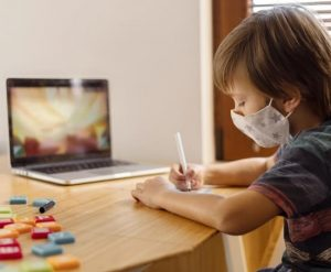 boy-wearing-medical-mask-attending-virtual-school
