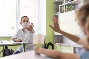 kids-waving-classroom-while-keeping-social-distance