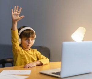 school-boy-yellow-shirt-taking-virtual-classes-raising-hand