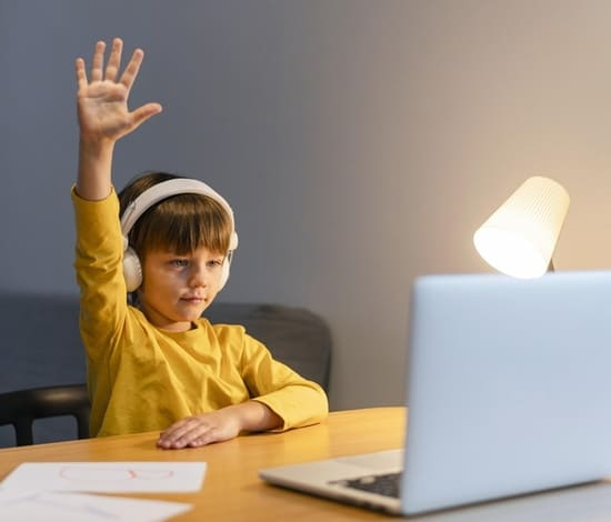 school-boy-yellow-shirt-taking-virtual-classes-raising-hand